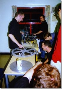 Several people operating a projector through a kitchen window by manually taking up film on a hand-driven rewind table